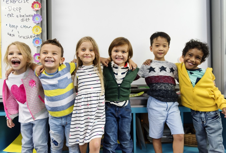 Group of diverse kindergarten students standing together in classroom
