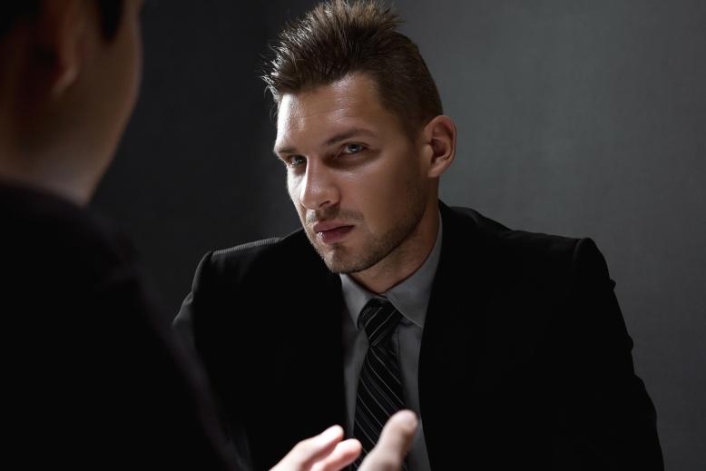 Detective interviewing suspect in dark interrogation room