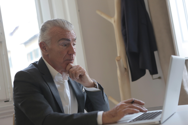 man-in-black-suit-jacket-using-laptop-computer-3789097